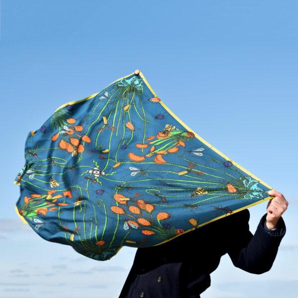 Homme caché par un grand foulard bleu qu'il tient devant lui, dans le vent
