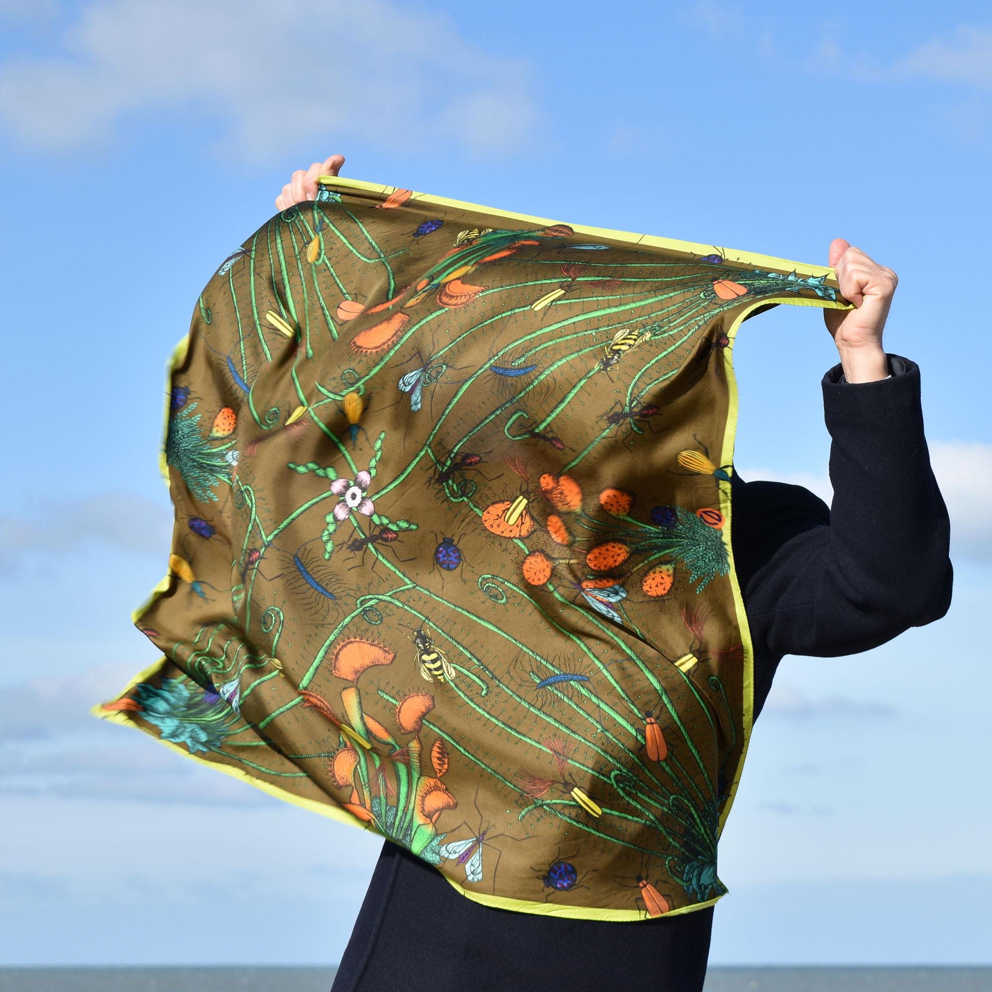 Homme caché par un grand foulard couleur café qu'il tient devant lui, par grand vent