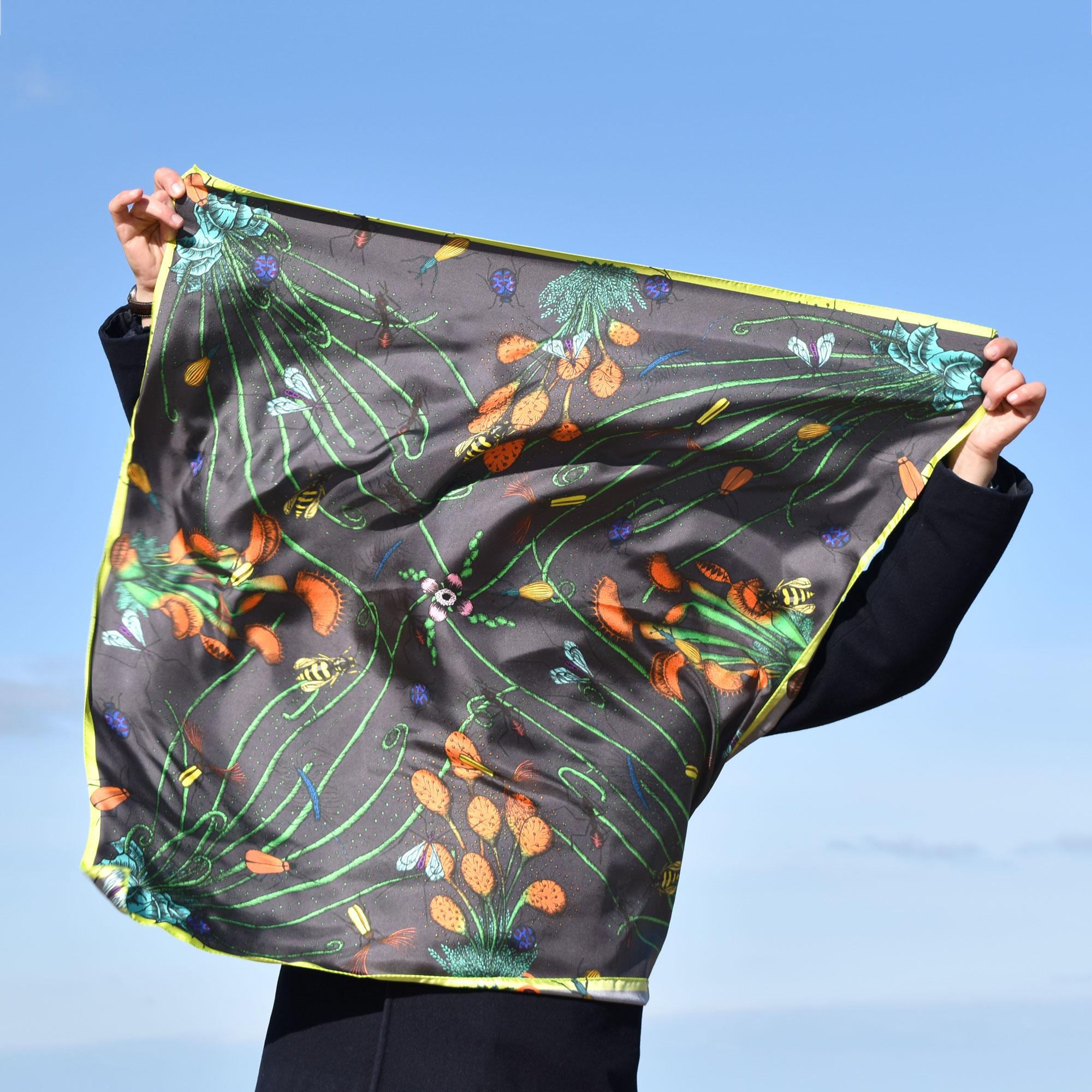 Homme caché par un grand foulard gris qu'il tient devant lui, par grand vent