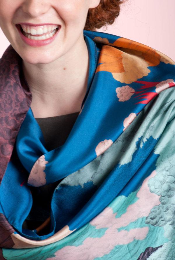 Gros plan sur foulard Volcan bleu noué et sur le sourire d'une femme