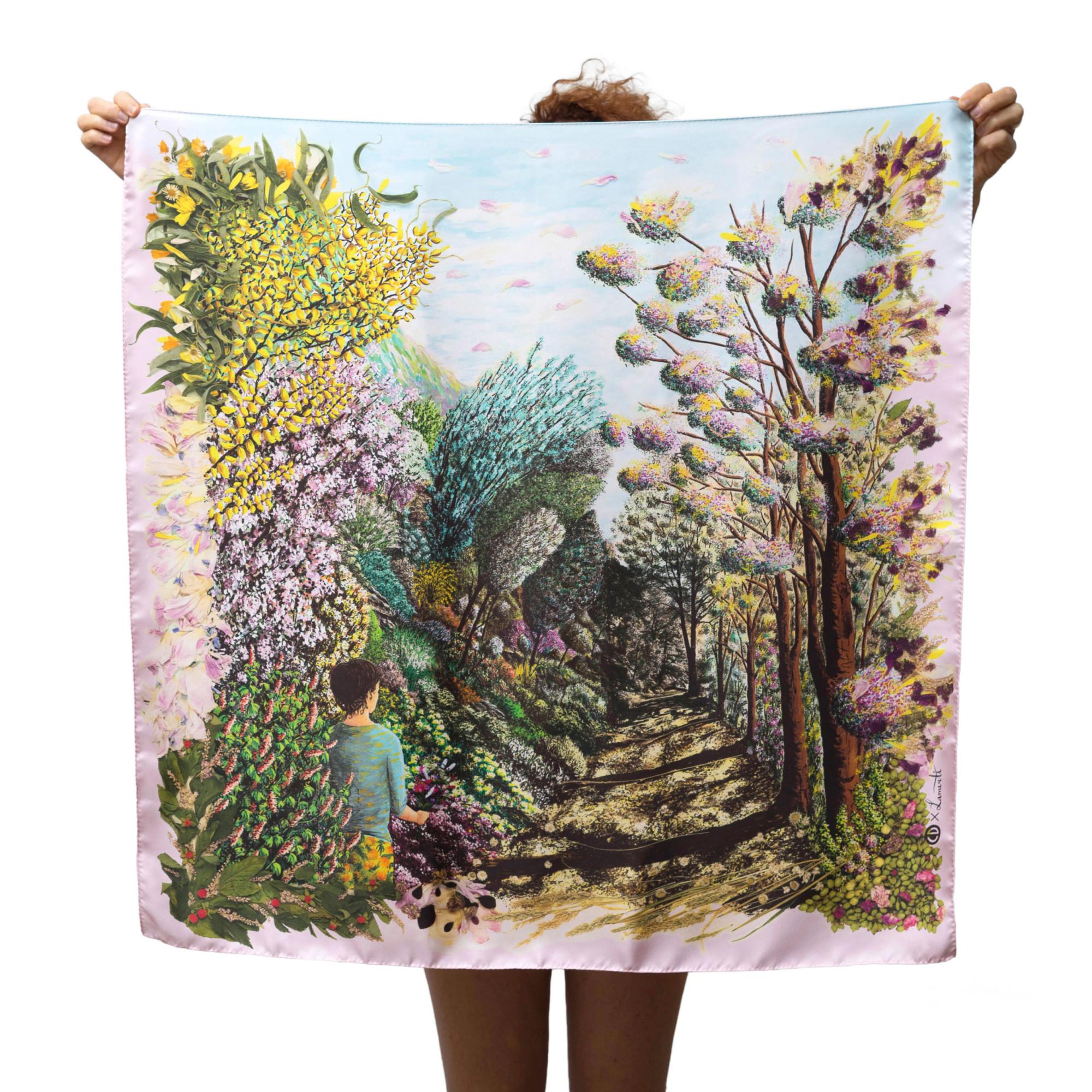 Grand foulard carré tenu déplié par une personne cachée. le foulard représente un paysage fleuri