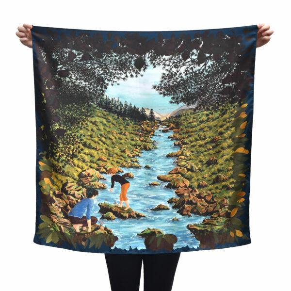 Grand foulard carré tenu déplié par une personne cachée. le foulard représente une rivière de montagne