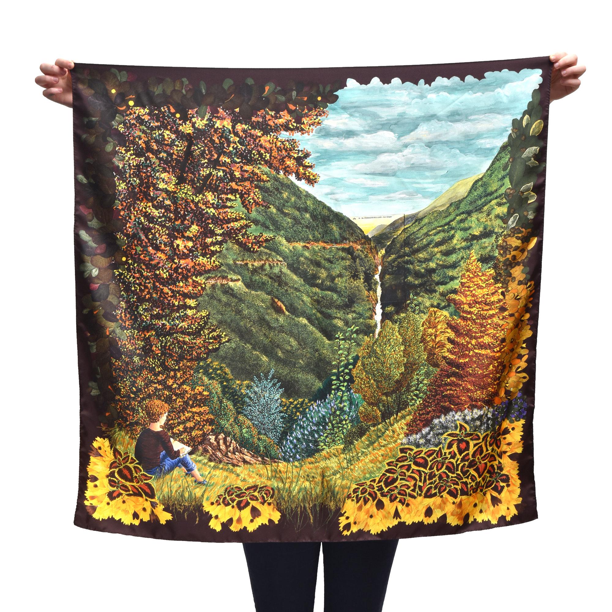 Grand foulard carré tenu déplié par une personne cachée. le foulard représente un paysage de montagne dans des tons d'automne