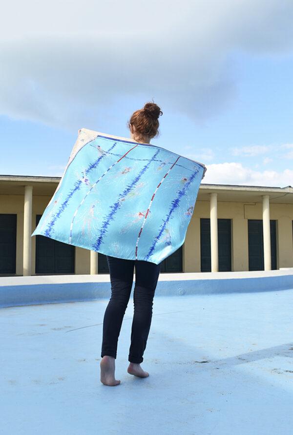 Jeune fille marchant de dos et tenant derrière elle un foulard comme une cape, représentant une piscine, dans un décor de piscine désaffectée (Deauville))