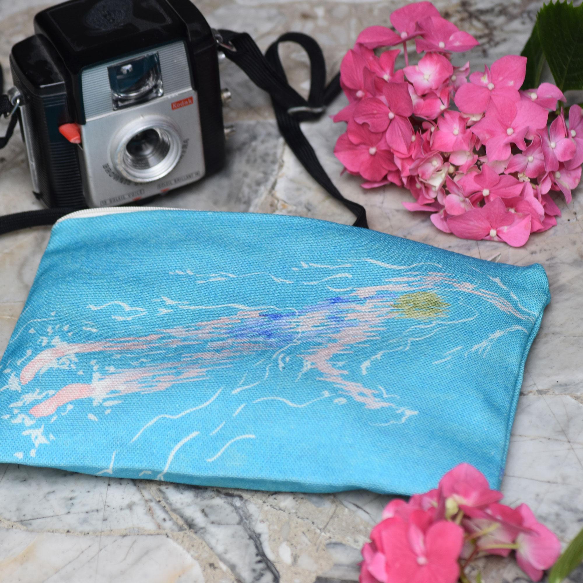 Pochette en tissu avec une fleur rose et un vieil appareil photo. Le motif sur la pochette représente une nageuse sur fond bleu
