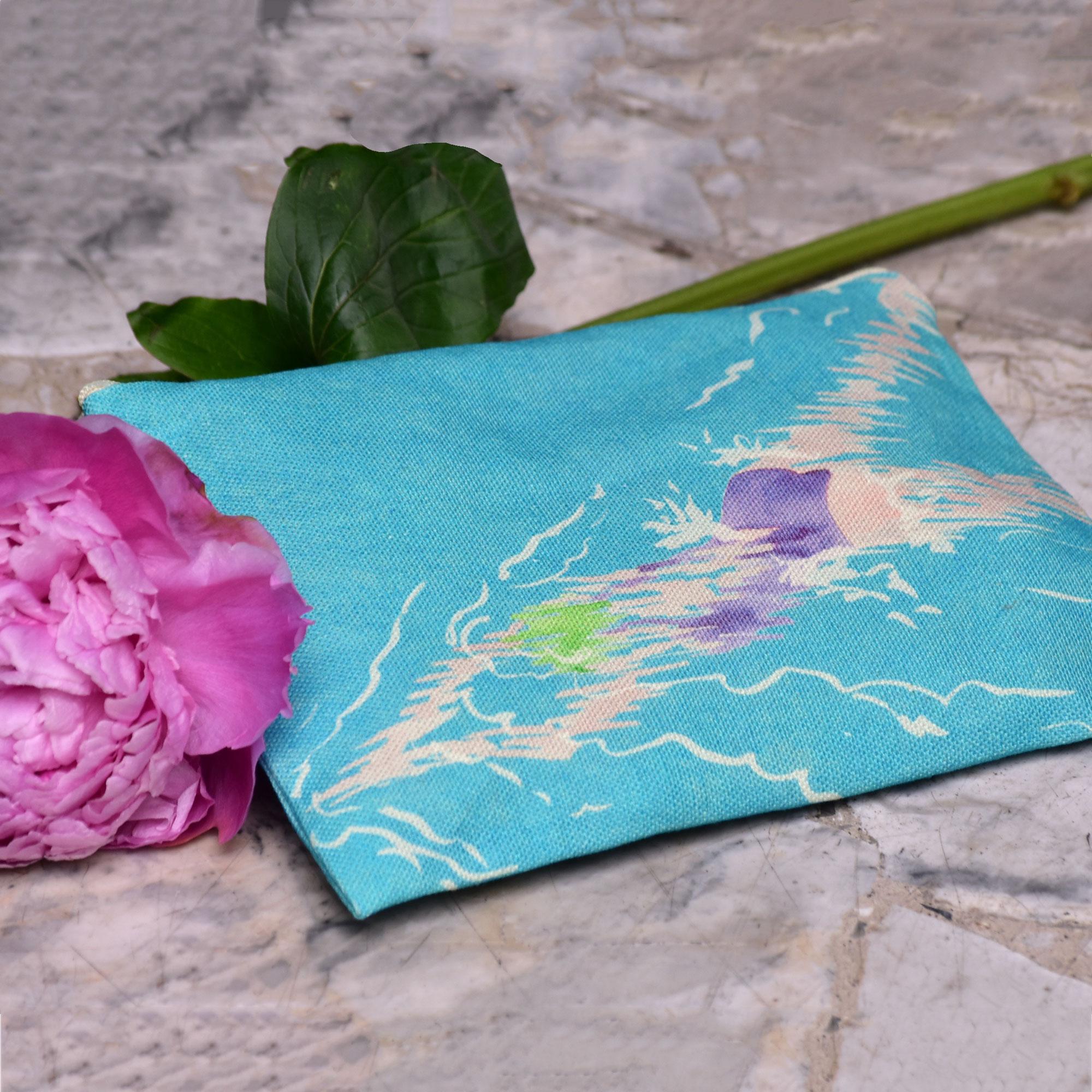 Pochette en tissu avec une fleur rose. Le motif sur la pochette représente une nageuse avec un maillot de bain violet sur fond bleu