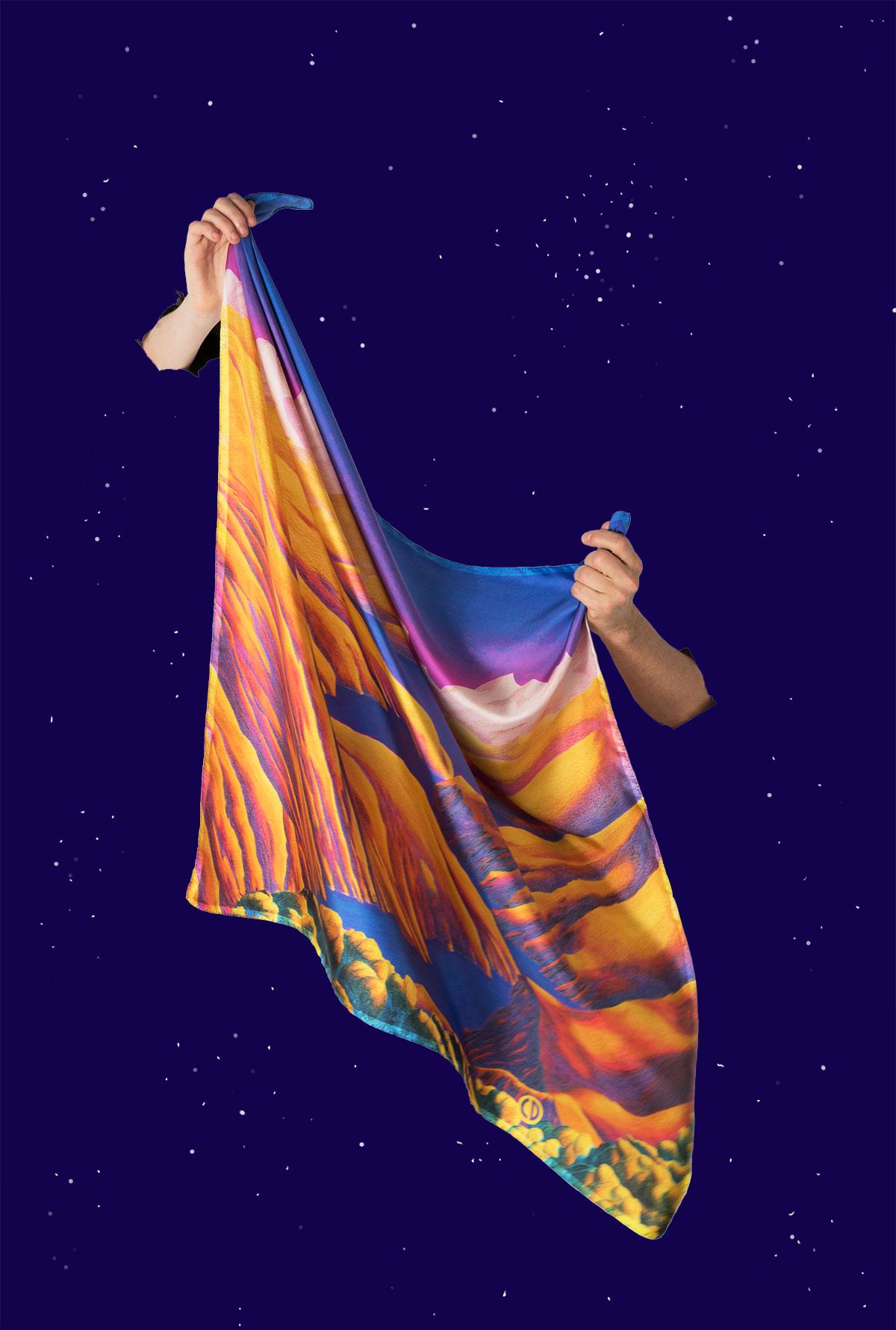 Foulard jaune orangé carré en soie tenu par deux mains semblant sortir d'un ciel étoilé