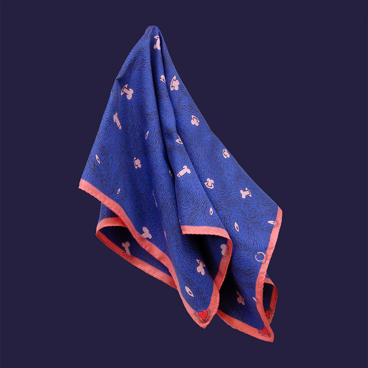 Petit foulard bleu nuit avec liseré rose accroché par la centre du foulard, sur fond uni