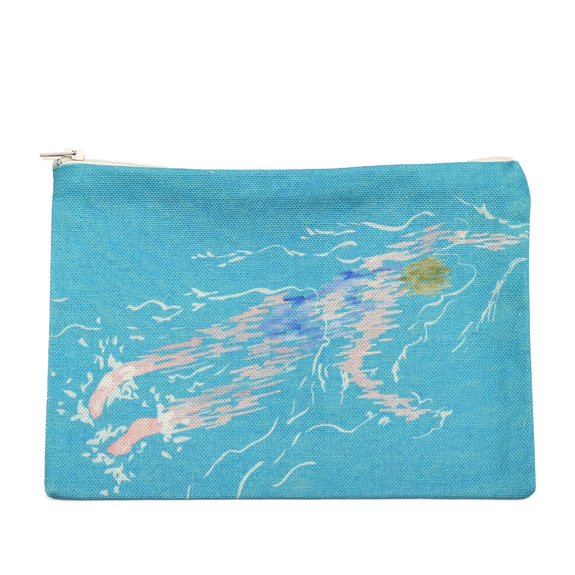 pochette à zip en tissu avec une paire de lunettes de soleil et une photographie argentique noir et blanc. Le motif sur la pochette représente une nageuse avec un maillot de bain bleu sur fond bleu