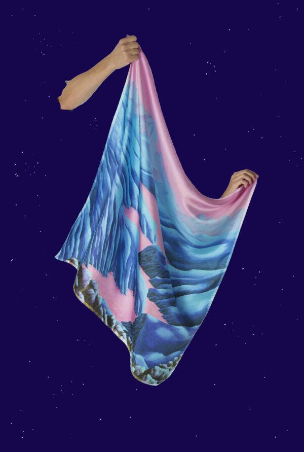Foulard bleu et rose carré en soie tenu par deux mains semblant sortir d'un ciel étoilé