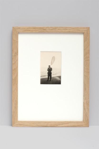 Collage sur photographie argentique noir et blanc représentant un homme debout sur une plage, une aile de libellule transparente figurant la fumée au dessus de la cigarette qu'il allume