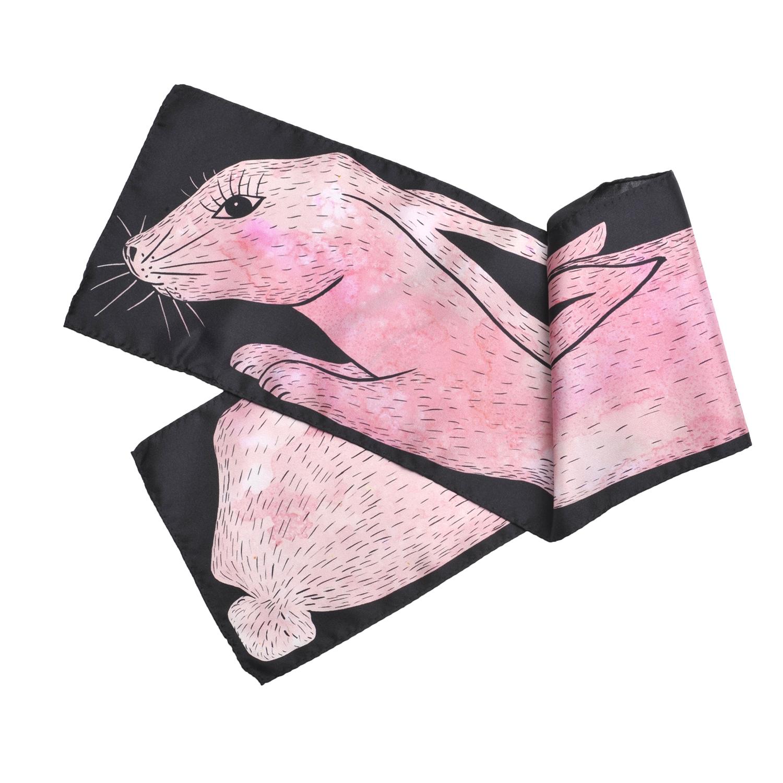 Foulard en soie plié de Céline Dominiak représentant un lapin rose dessiné sur fond noir