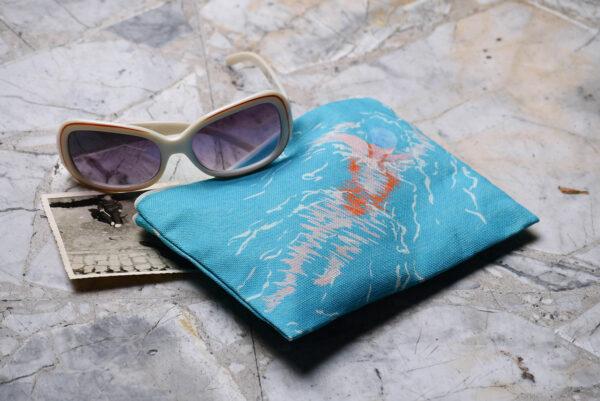 Mise en scène d'une pochette à zip en tissu avec une paire de lunettes de soleil et une photographie argentique noir et blanc. Le motif sur la pochette représente une nageuse avec un maillot de bain orange sur fond bleu