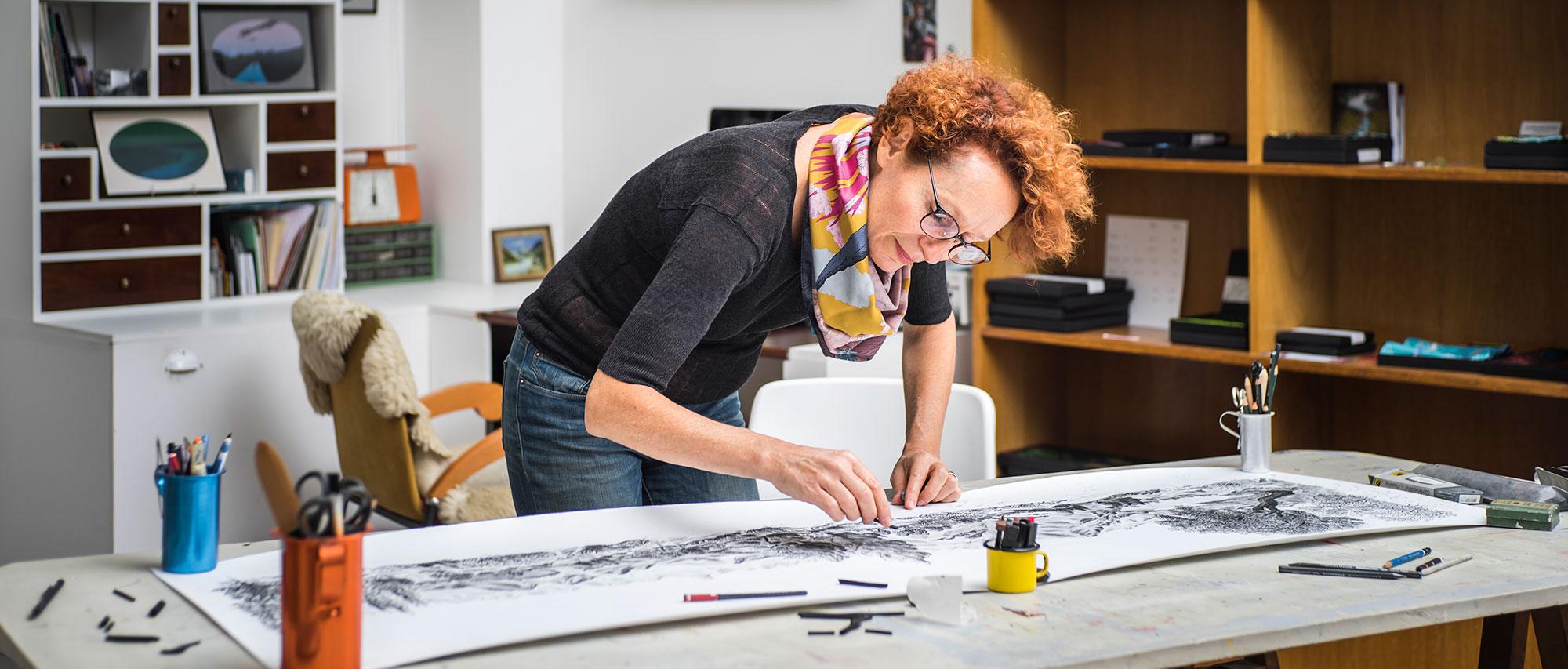 Dans un atelier d'artiste, Céline Dominiak est debout, en train de dessiner, penchée sur un grand dessin au fusain. elle porte un foulard.