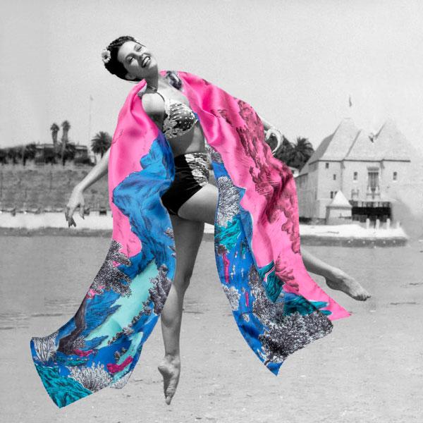 Photographie noir et blanc d'une jeune femme sautant sur la plage jouant avec un grand foulard rose et bleu - photomontage