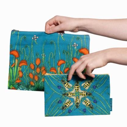 Deux pochettes tailles M et L de la collection Carnivore de Céline Dominiak, avec des insectes et des plantes carnivores sur fond bleu, recto