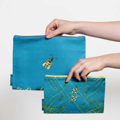Deux pochettes tailles M et L de la collection Carnivore de Céline Dominiak, avec des insectes et des plantes carnivores sur fond bleu, verso