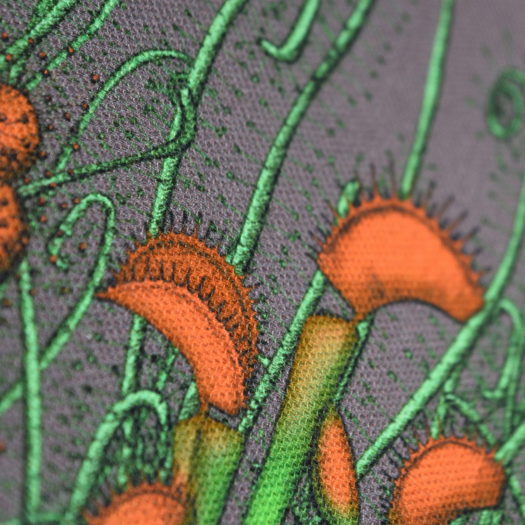 Détail d'une pochette taille L de la collection Carnivore de Céline Dominiak, avec des insectes et des plantes carnivores sur fond gris, recto