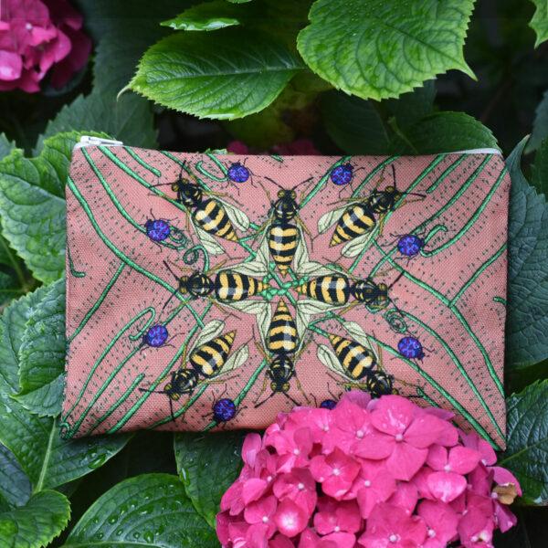 Une pochette taille M de la collection Carnivore de Céline Dominiak, avec des insectes et des plantes carnivores sur fond rose, recto