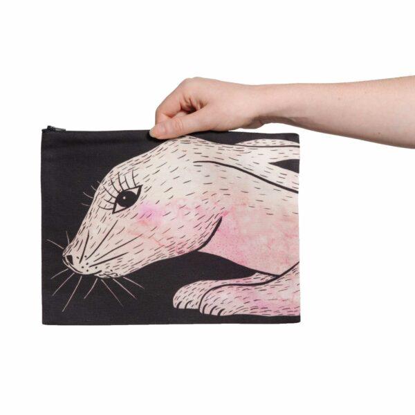 Une pochette taille L de la collection Fourrure de Céline Dominiak, avec une tête de lapin rose sur fond noir, recto