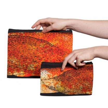 Deux pochettes tailles M et L de la collection Fourrure de Céline Dominiak, avec queues de renard orange sur fond noir, verso