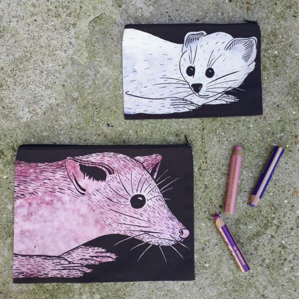 Deux pochettes tailles M et L de la collection Fourrure de Céline Dominiak, une avec une tête de martre rose sur fond noir, l'autre avec une tête d'hermine blanche sur fond noir, recto